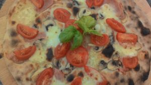 Pizza con Mozzarella Funghi Prosciutto e Pomodorini